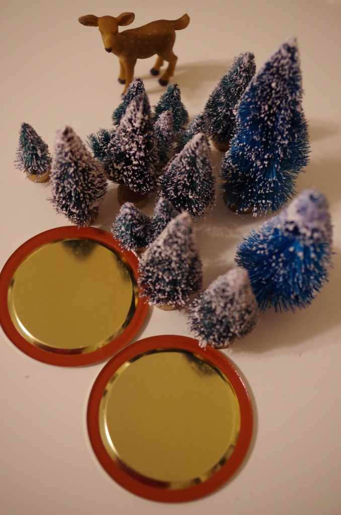 "The most important supplies, really, are the festive things that go inside the snow globe, because that's what makes the snow globe festive and festivity? It's important. Here, I've gathered a bunch of little trees which are apparently called ""bottle-brush trees."" That's your craft fact for the day. You're welcome. I read somewhere on the Internets that these can discolor the snow globe water, so I sprayed them with acrylic top-coat sealer. I'm not sure if that's actually going to be effective, but it made me feel useful and pro-active and really, let's be honest, it's the holidays, and anything that makes you feel useful and pro-active is important."
